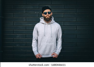City portrait of handsome hipster guy with beard wearing gray blank hoodie or hoody with space for your logo or design and casual beanie. Mockup for print