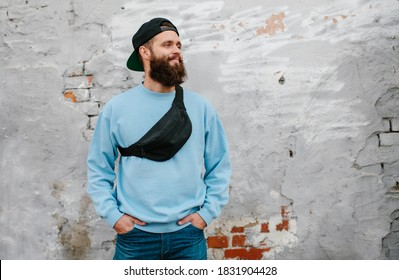 City portrait of handsome hipster guy with beard wearing blue blank sweatshirt with black waist bag with space for your logo or design. Mockup for print