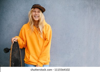 City portrait of positive young female wearing orange hoody and baseball cap holding skateboard. Grey blue wall on background