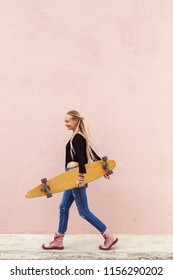 City portrait of positive young female  holding skateboard. Pink wall on background