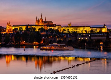 City of Prague at evening twilight in Czechia (Czech Republic), illuminated the Castle with reflection in river Vltava.