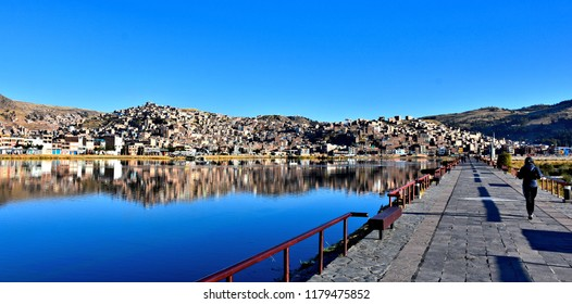 City of Puno reflected in Tranquil waters of lake Titicaca. Puno - capital city of the Puno Region - important regional center and major tourist destination in Peru. Photo taken 2018-08-27.