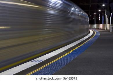 city rail train night traffic arrives station platform blurred motion