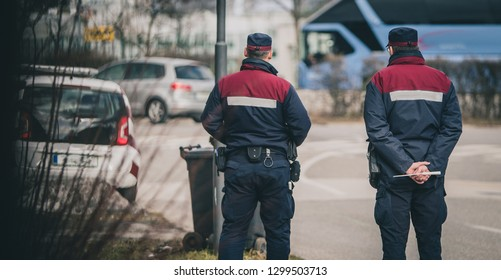 City rangers or redar on a mission to stop and fine speeding cars. Speed control in the city with uniformed people or police officers. Back view of officers stopping too fast cars.