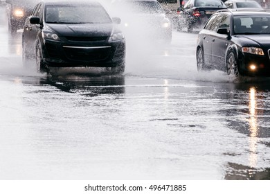 city road during heavy rain. car traffic driving on flooded street.