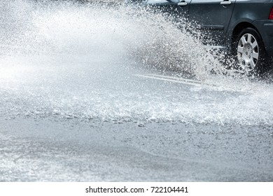 city road flooded with rainwater. splashing car on wet street.