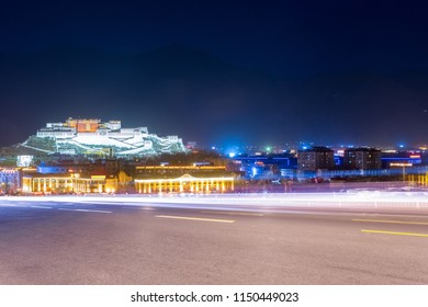 city road in lhasa , night view of the potala palace , tibet