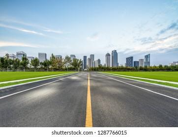 city road through modern buildings under blue sky