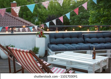 City rooftop terrace with palette furniture, herbal garden and bunting flags