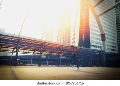 City Running - asian woman runner and bangkok skyline. Female athlete fitness jogging living healthy lifestyle