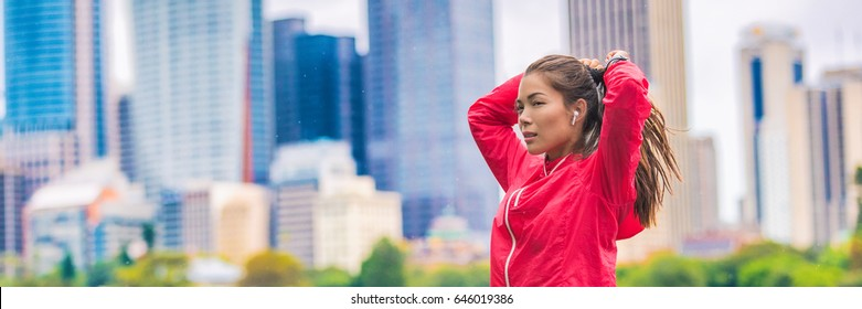 City running healthy lifestyle banner runner woman tying ponytail hair getting ready to run in urban background. Horizontal panorama crop. Asian sport girl.