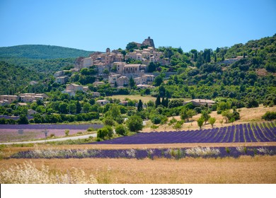 City of Saint-Saturnin-les-Apt on the hill with lavender fields in valley on summer day. Provence, France