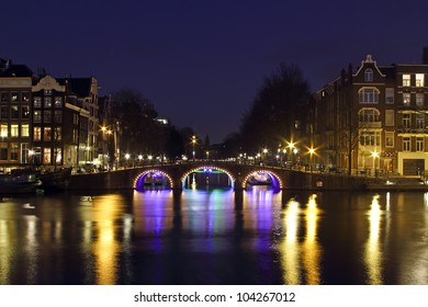 City scenic from Amsterdam by night at the river Amstel in the Nethrlands