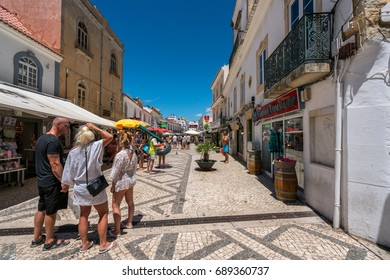 City shopping street. Albufeira, Portugal - July 19, 2017: Perspective view of the old parts of Albufeira with tourists shopping and some about to go to the beach. Shops and restaurants on the street.