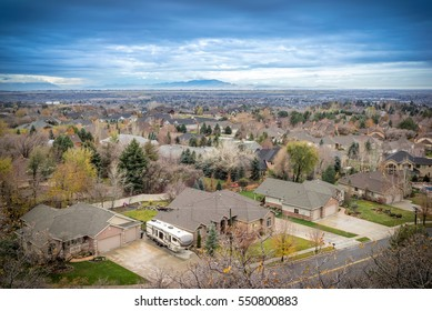 City Sky Line with Dark, Cloudy Sky, Rooftops Distant Mountains, Bare Trees - Ogden, Utah.