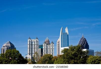 The city skyline against a blue sky over trees
