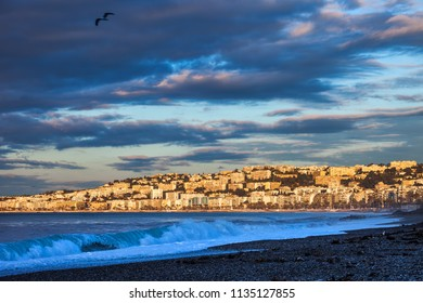 City skyline of Nice at sunrise in France, view from French Riviera beach at Mediterranean Sea