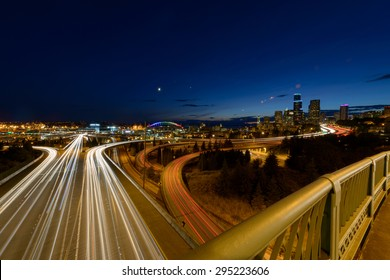 City skyline at night with car lights streaking on highway