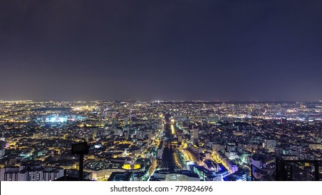 The city skyline at night. Paris, France. Taken from the tour Montparnasse panorama timelapse traffic 4K view on railway station with trains