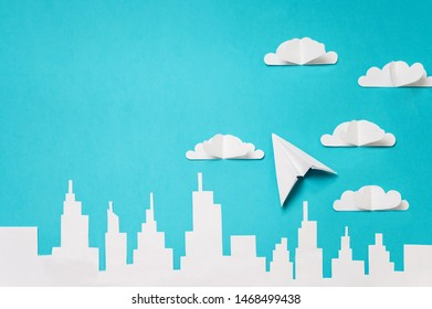 City skyline and origami plane in clouds. Craft paper objects photography for banners/landing pages/backgrounds design with copy space.