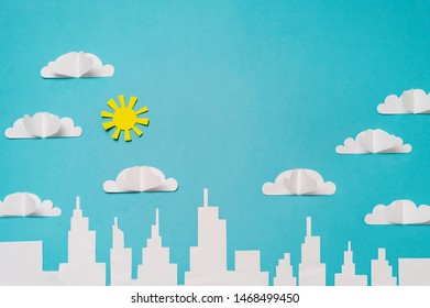 City skyline with paper cut clouds and sun. Craft paper objects photography for banners/landing pages/backgrounds design with copy space.