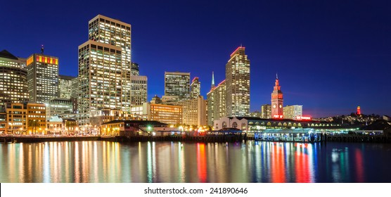 City skyline in San Francisco, California. Many buildings are illuminated with red and gold lights in honor of the 49ers making the NFL playoffs.