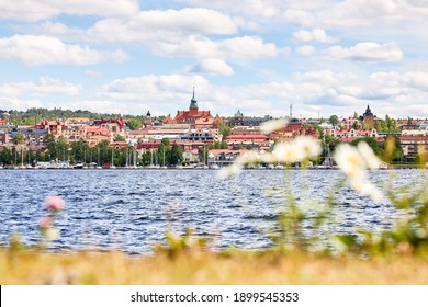 Östersund's city skyline seen from the island Frösön with some out of focus vegetation in foreground. In between lies the lake Storsjön.
