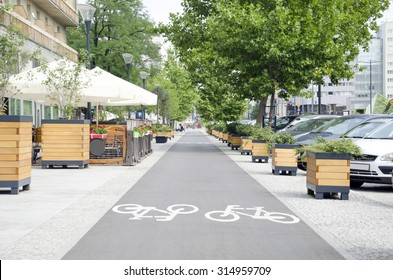 City street with long bicycle lane near outdoor cafe