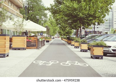 City street with long bicycle lane near outdoor cafe; Vintage effect