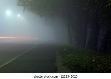 city street at night in heavy fog, traces of headlights of cars on a long exposure