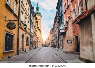 City street of old town in Warsaw. Narrow sunny street between colorful buildings of old town