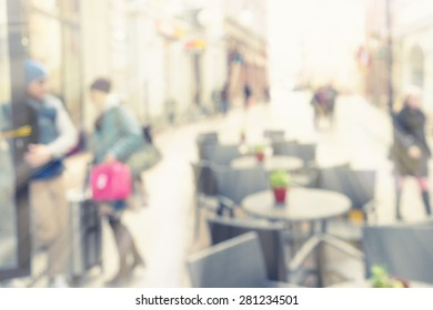 City street with people in the spring in a blurred in the sun