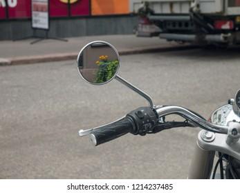 City street scene: yellow flowers mirroring at bike mirror