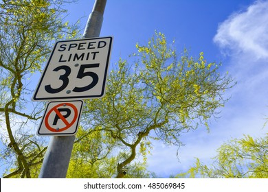 City street Speed Limit sign and No Parking sign on a light pole