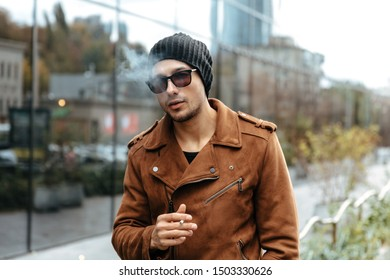 City style. Fashion. Handsome young man in jacket, cap and sunglasses is smoking while walking in the city