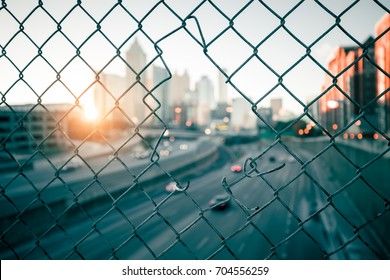 City sunrise skyline through the wire mesh fence. Abstract blurred cityscape background