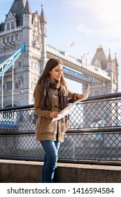 City tourist concept: attractive city traveler woman looks at the map in front of Tower Bridge in London,UK