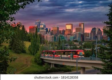 A city train commuting under a cloudy sunrise sky in Calgary
