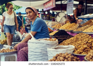 The city of Turgutreis , Bodrum, Turkey - 2018. The coast of the Aegean Sea.  A beautiful woman in traditional clothes sells nuts and oriental sweets in the market in Turkey.