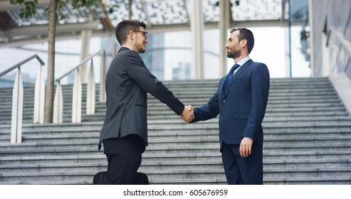 In the city two businessman they shake hands and smile before starting to collaborate on a project. Concept: teamwork, business, contract, bank.