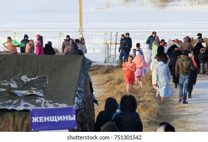 The city of Tyumen, Russia, January 19, 2017: Women run on straw after swimming in cold water. Orthodox Tyumen on the day of baptism.