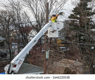 City utility electrician worker connects wires to new led street light, Revere Massachusetts USA, February 12, 2020