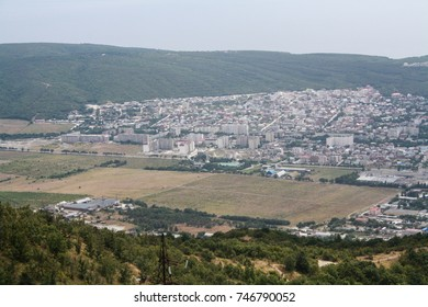 The city in the valley of the mountains. City view from a high mountain. On the rocks grows the forest.