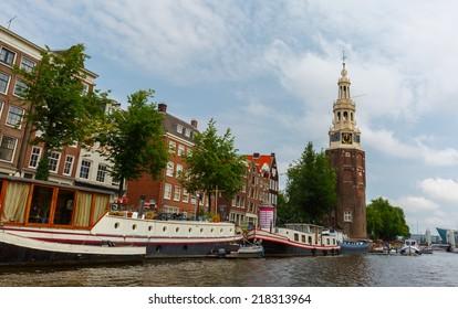City view of Amsterdam canal Oudeschans and tower Montelbaanstoren, Holland, Netherlands.