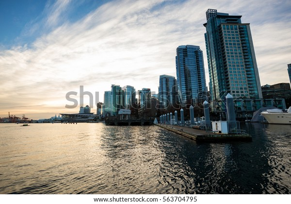 City view of Downtown Vancouver from Coal Harbour. Picture taken during a cloudy winter sunrise.