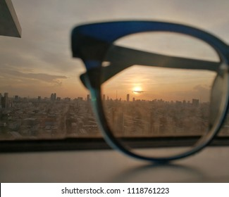 City view focused on glasses lenses with sunset.