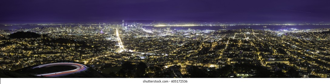 City view at night of San Francisco.  The aerial skyline shows both the financial district or downtown as well as urban residential housing in Oakland and SF. The image depicts tourism in America.