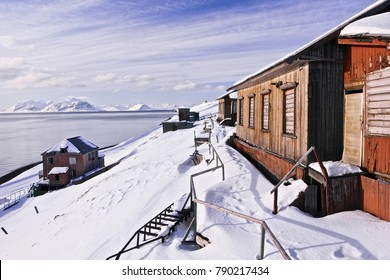 The city view of russian (soviet) Barentsburg with arctic coal mining station, Svalbard. Snow mountain peaks on the horizon, old abandoned houses, silence and calm, sunny good weather day, background.