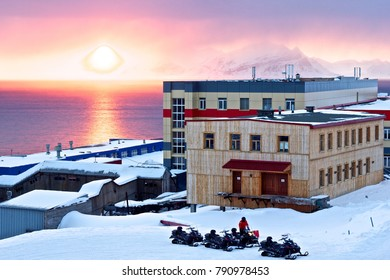 The city view of russian (soviet) Barentsburg , Svalbard. Snow mountain peaks on the horizon, sun circle,houses and snowmobiles, silence and calm, background. Beautiful arctic sunset, spring sunny day
