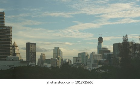 City view in soften color, blue sky with many high buildings and parks, modern architecture and urban life in the town, it is Bangkok metropolis, capital of Thailand